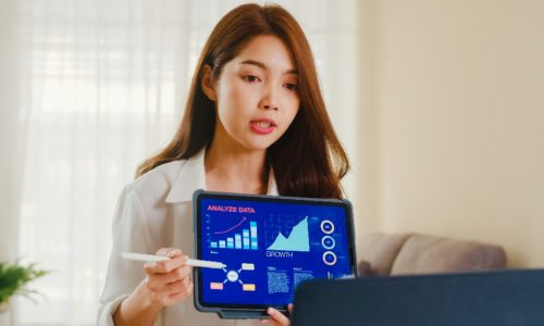 Asia businesswoman using laptop and tablet presentation to colleagues about plan in video call while working from home at living room. Self isolation, social distancing, quarantine for coronavirus.