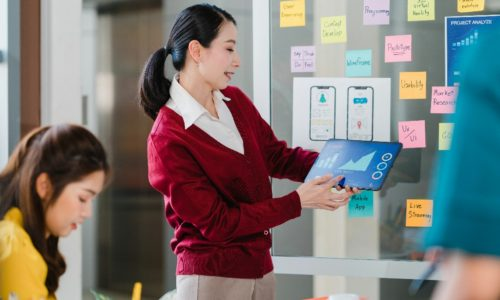 Group of Asia young creative people meeting brainstorming ideas conducting business presentation ideas mobile application software design project colleagues in modern office. Coworker teamwork concept
