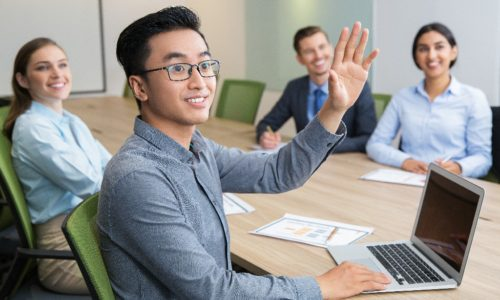Young Asian businessman wearing glasses sitting at meeting or conference in boardroom with multiethnic colleagues and raising hand to ask question